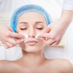 Skin care - woman cleaning face by beautician